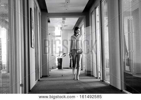 Full length of young businesswoman walking in office corridor