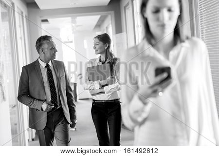 Business people walking in corridor with female colleague using mobile phone in foreground at office