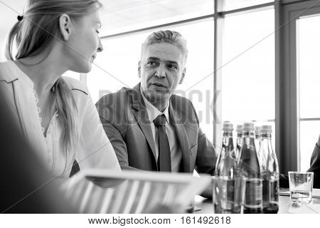 Mature businessman discussing with female colleague in board room
