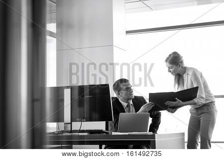 Businesswoman showing file to businessman at desk in office