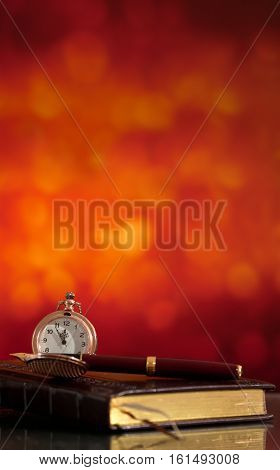 Notebook and pocket watch on the bright blurred background with bokeh