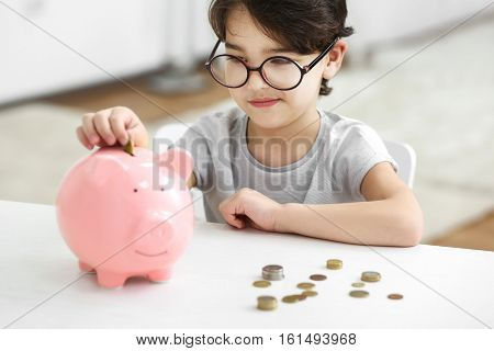 Portrait of cute little boy in glasses putting coin into a piggy bank on blurred background