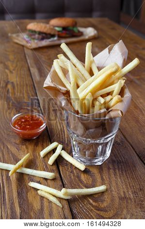 French fries in glass and burger unfocused. Fast food take away on rustic wood. Fried potato chips with tomato sauce.