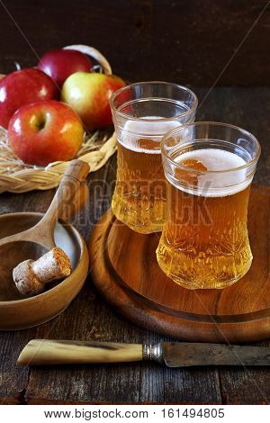 Two cups of Apple Cider and red apples in wicker basket