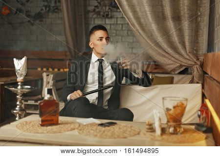 Young Rich Man In An Elegant Suit Has A Rest In A Bar And Smokes A Hookah.