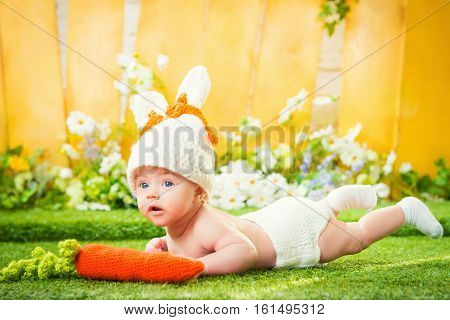 happy baby child in costume a rabbit bunny with carrot.