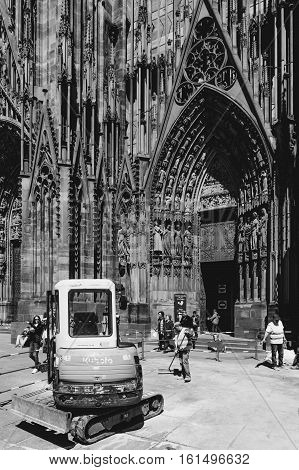STRASBOURG FRANCe - MAY 04 2016: Black and white photograph of Kubota tractor arranging granite pavement sones in from of Strasbourg Cathedral