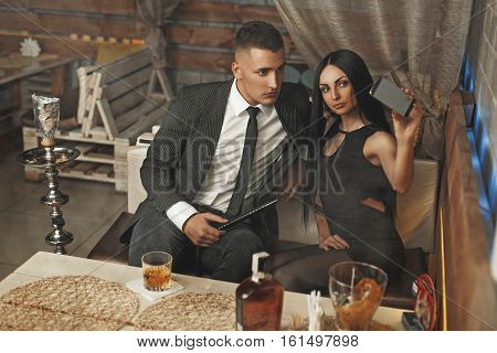 Beautiful Elegant Young Couple Relaxing In A Bar And Smokes A Hookah. Are Photographed Themselves On