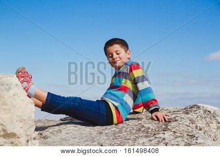 boy sitting on a rock holding up his feet on the stone and close eyes