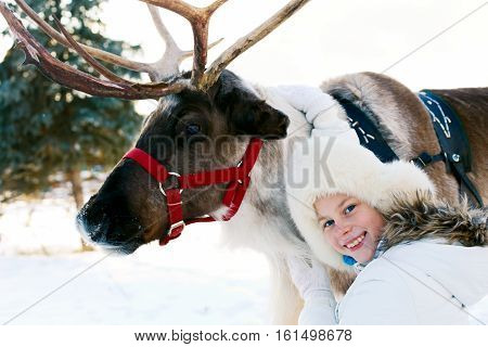 Happy little girl hugging her reindeer. Winter playtime.