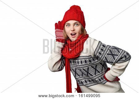 Surprised emotional young woman in winter warm clothing listening gossip with palm at ear looking out of frame