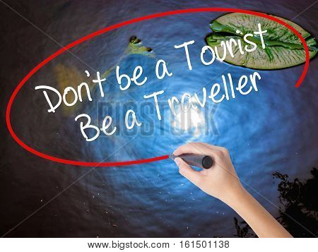 Woman Hand Writing Don't Be A Tourist Be A Traveller  With Marker Over Transparent Board