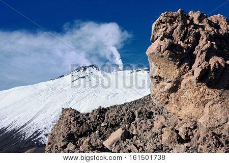 volcanic rock on background snowy Etna emit smokes, Sicily