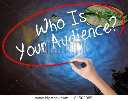 Woman Hand Writing Who Is Your Audience? With Marker Over Transparent Board