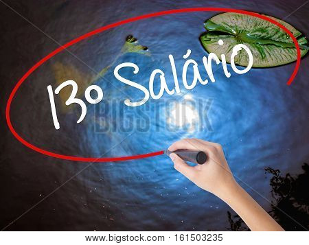 Woman Hand Writing 13 Salary (13O Salario In Portuguese)  With Marker Over Transparent Board