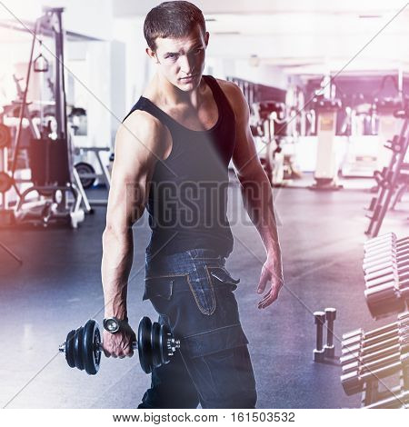 Young muscular man. Bodybuilder working out with bumbbells weights at the gym