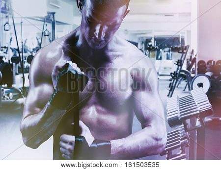 Young muscular man. Bodybuilder working out at the gym