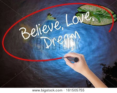 Woman Hand Writing Believe Love Dream With Marker Over Transparent Board