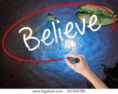 Woman Hand Writing Believe With Marker Over Transparent Board