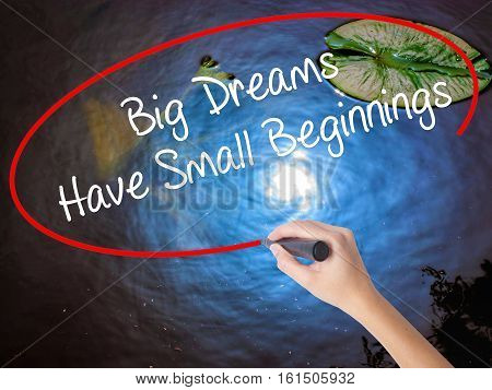 Woman Hand Writing Big Dreams Have Small Beginnings With Marker Over Transparent Board