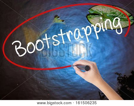 Woman Hand Writing Bootstrapping With Marker Over Transparent Board