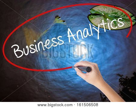 Woman Hand Writing Business Analytics With Marker Over Transparent Board