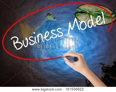 Woman Hand Writing Business Model With Marker Over Transparent Board.