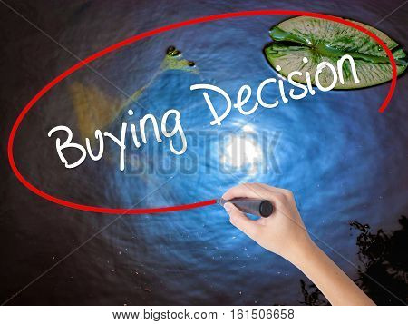 Woman Hand Writing Buying Decision With Marker Over Transparent Board.