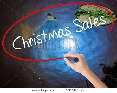 Woman Hand Writing Christmas Sales With Marker Over Transparent Board