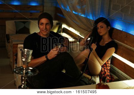 Beautiful Young Couple Relaxing In A Bar. Girl Smokes A Hookah, Man Drinks Whiskey.