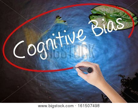 Woman Hand Writing Cognitive Bias With Marker Over Transparent Board