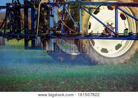 closeup view of tractor spraying wheat field with sprayer