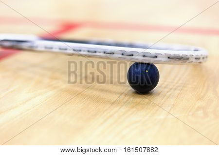 Close up of a squash racket and ball on the wooden background. Racquetball equipment. Squash ball between squash racket and floor on the court. Photo with selective focus