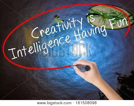 Woman Hand Writing Creativity Is Intelligence Having Fun With Marker Over Transparent Board