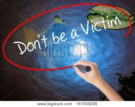 Woman Hand Writing Don't Be A Victim  With Marker Over Transparent Board