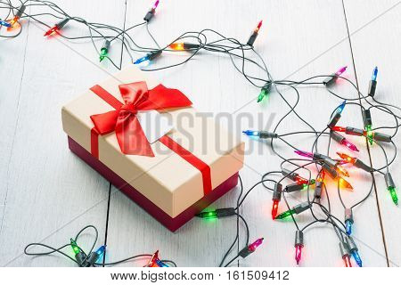 Gift And Blinker Light Lamp On White Wooden Background