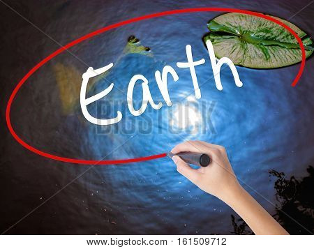Woman Hand Writing Earth With Marker Over Transparent Board.