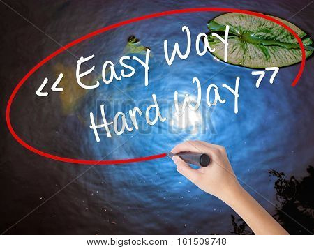 Woman Hand Writing Easy Way - Hard Way With Marker Over Transparent Board.
