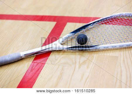 squash racket and ball on the wooden background. Racquetball equipment. Squash ball and squash racket on the court next to a red line. Photo with selective focus