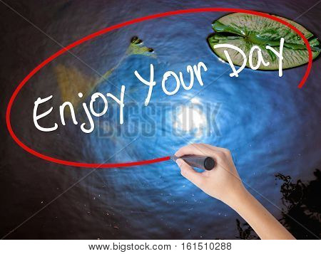 Woman Hand Writing Enjoy Your Day With Marker Over Transparent Board