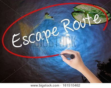 Woman Hand Writing Escape Route With Marker Over Transparent Board