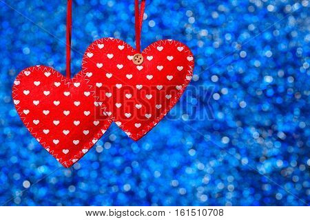 two sewn hearts hanging against blue bokeh background. Valentine theme - red felt hearts with thread. Decorative textile hearts. Idea for Valentine's Day greeting card. Photo with place for text