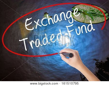 Woman Hand Writing Exchange Traded Fund With Marker Over Transparent Board.