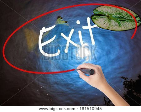 Woman Hand Writing Exit With Marker Over Transparent Board