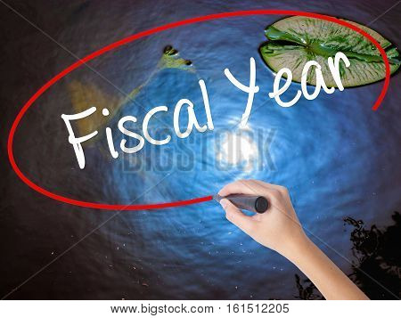 Woman Hand Writing Fiscal Year With Marker Over Transparent Board.