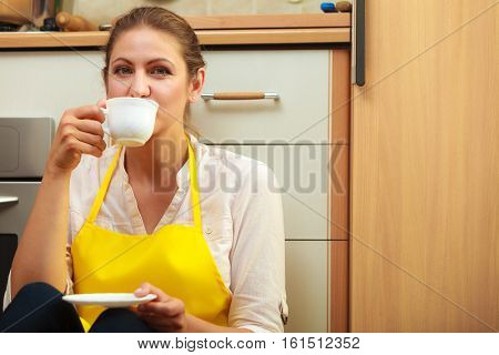 Mature woman in apron drinking cup of coffee in kitchen. Housewife female relaxing resting sitting on floor.