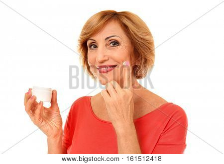 Portrait of senior woman applying anti-aging cream onto face, isolated on white