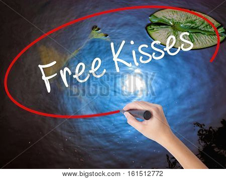 Woman Hand Writing Free Kisses  With Marker Over Transparent Board