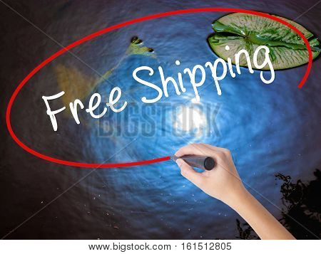 Woman Hand Writing Free Shipping With Marker Over Transparent Board