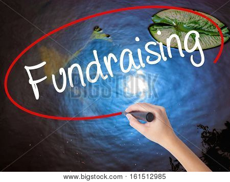 Woman Hand Writing Fundraising With Marker Over Transparent Board